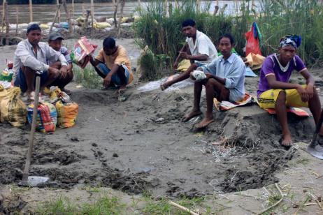 Break: Local farmers take a rest, even as the river continues to rise, from their desperate attempt to embank the Budhi Kulo before their fields are lost to sand.
