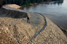 Shifting Path: Man walking on the newest extension of the Karnali River Training Project. This embankment is still mostly loose sand and stone excavated from the river itself that must be reinforced with gabion wire